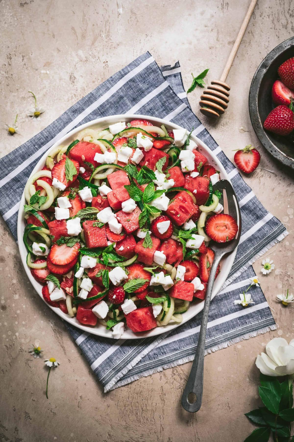 overhead view of watermelon strawberry cucumber salad with mint and feta on white plate