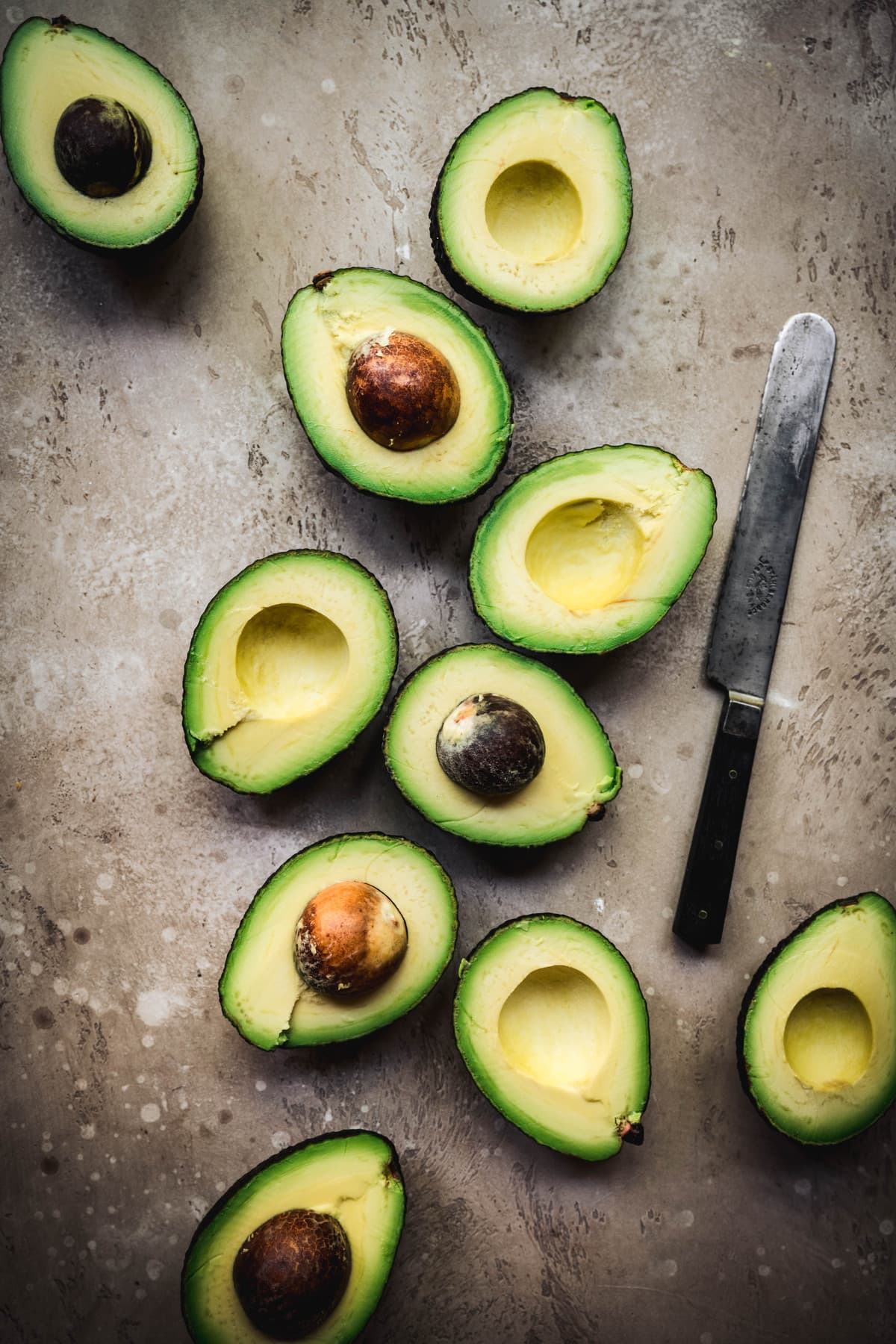 Beautiful photo of avocados sliced in half on a rustic background