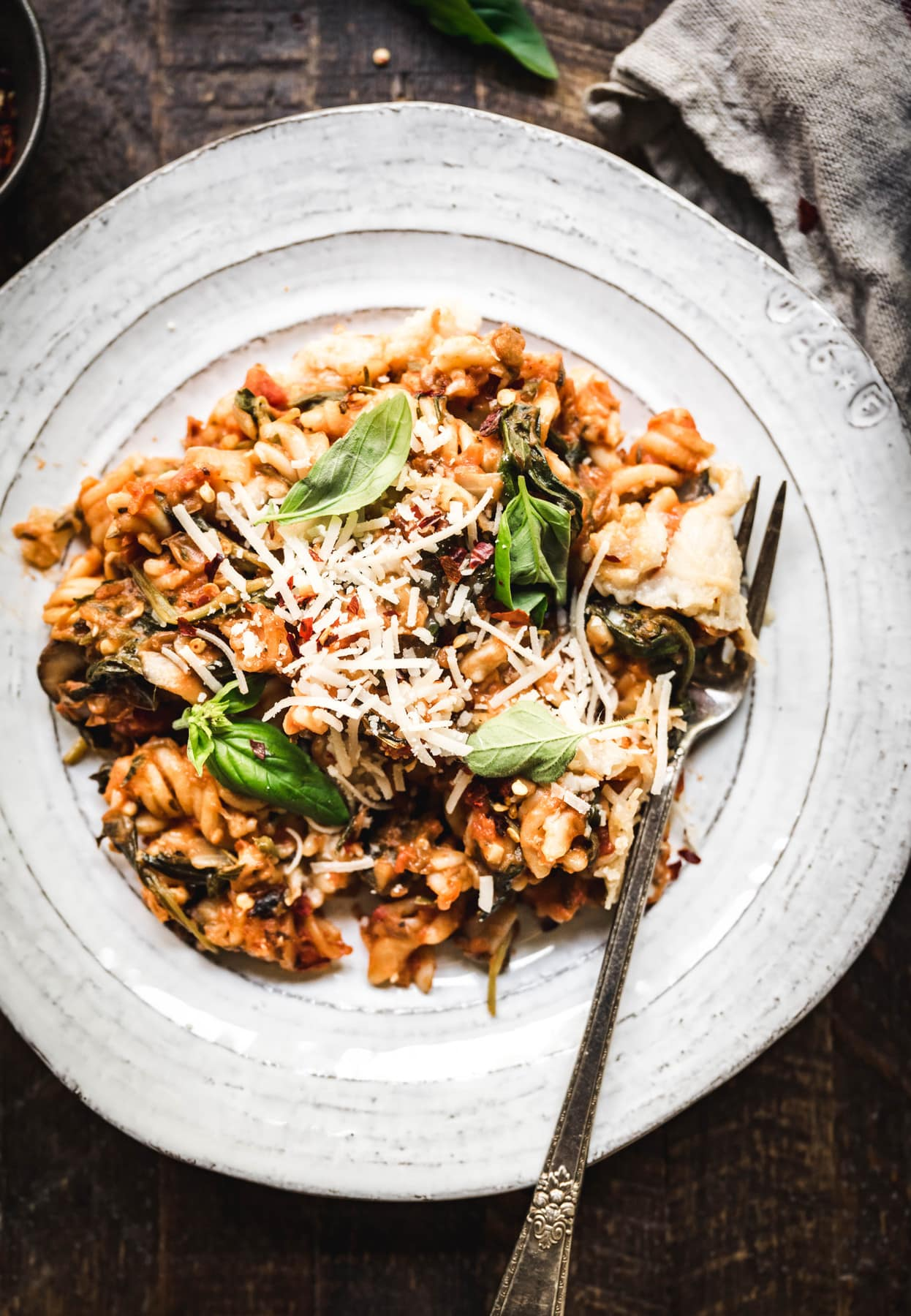 overhead view of healthy vegan gluten free pasta bake on a white plate with fork