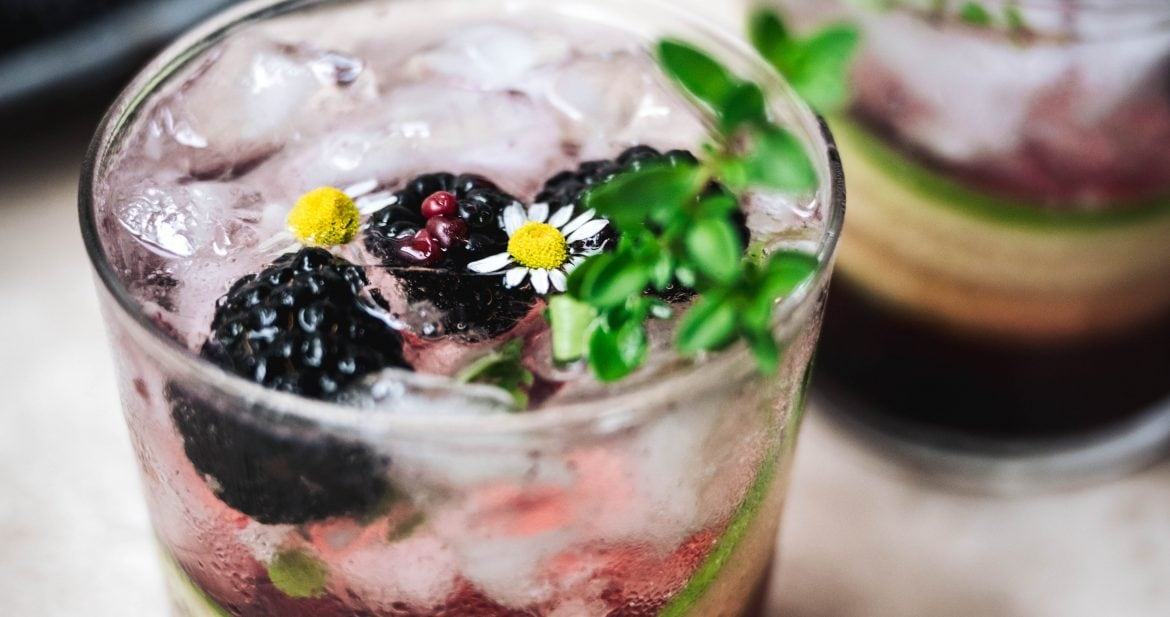 45 degree angle of blackberry cucumber gin cocktails with fresh herb garnish