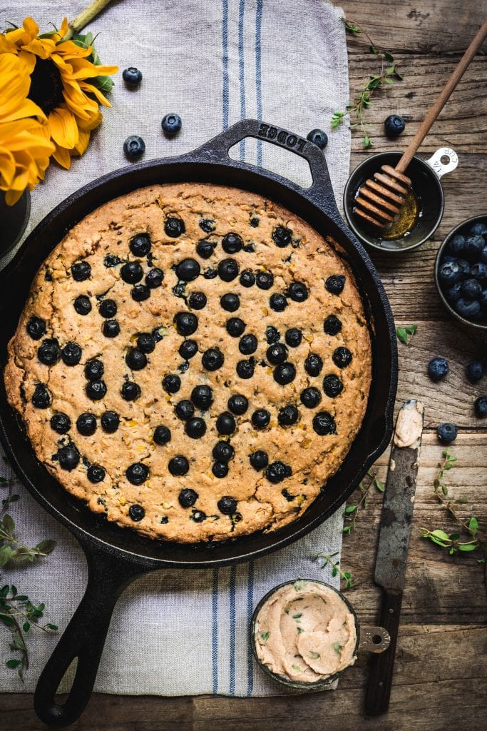 overhead of vegan blueberry cornbread in a skillet with homemade vegan honey thyme butter on the side