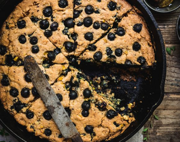 overhead of gluten free blueberry cornbread in a cast iron skillet with a slice removed