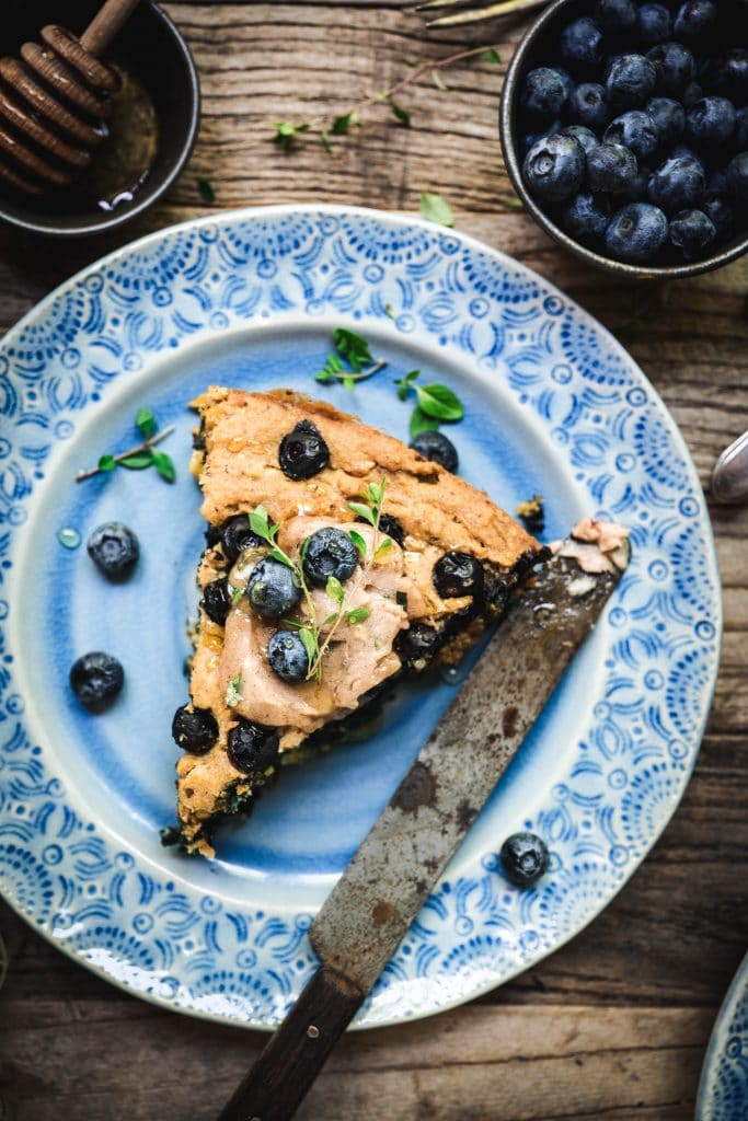 overhead of a slice of gluten free blueberry cornbread on a blue plate with a butter knife