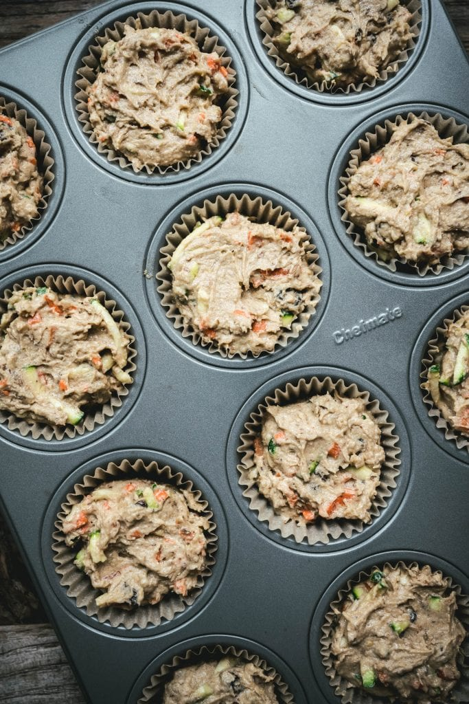 overhead of vegan zucchini muffin batter in muffin tins before it's baked