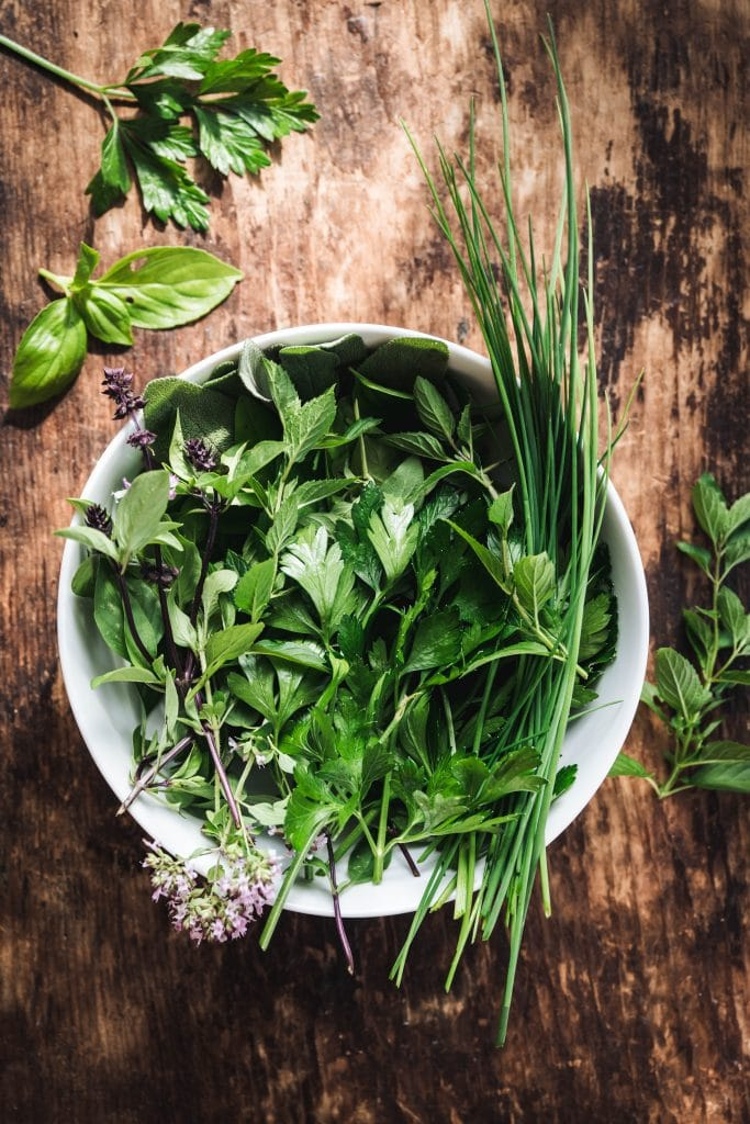 overhead of fresh herbs, oregano, basil, chives, cilantro, in a white bowl on a wooden background