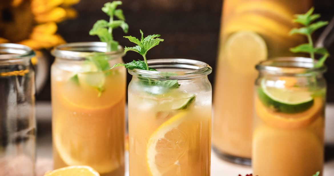 side view of long island iced tea garnished with fresh lemon and mint