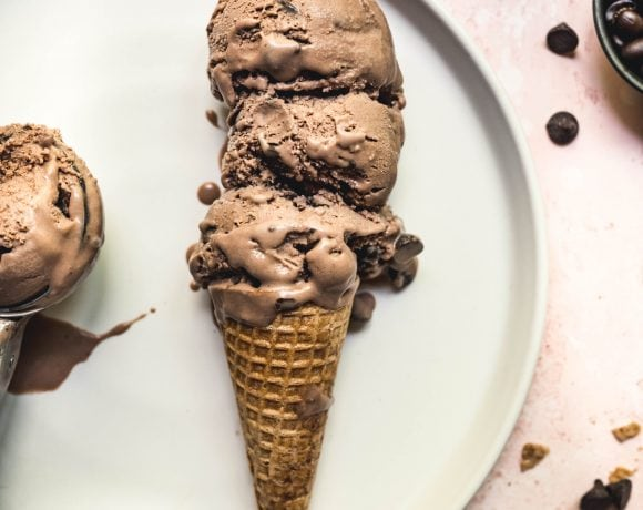 overhead of three scoops of vegan mocha ice cream in a cone on a white plate