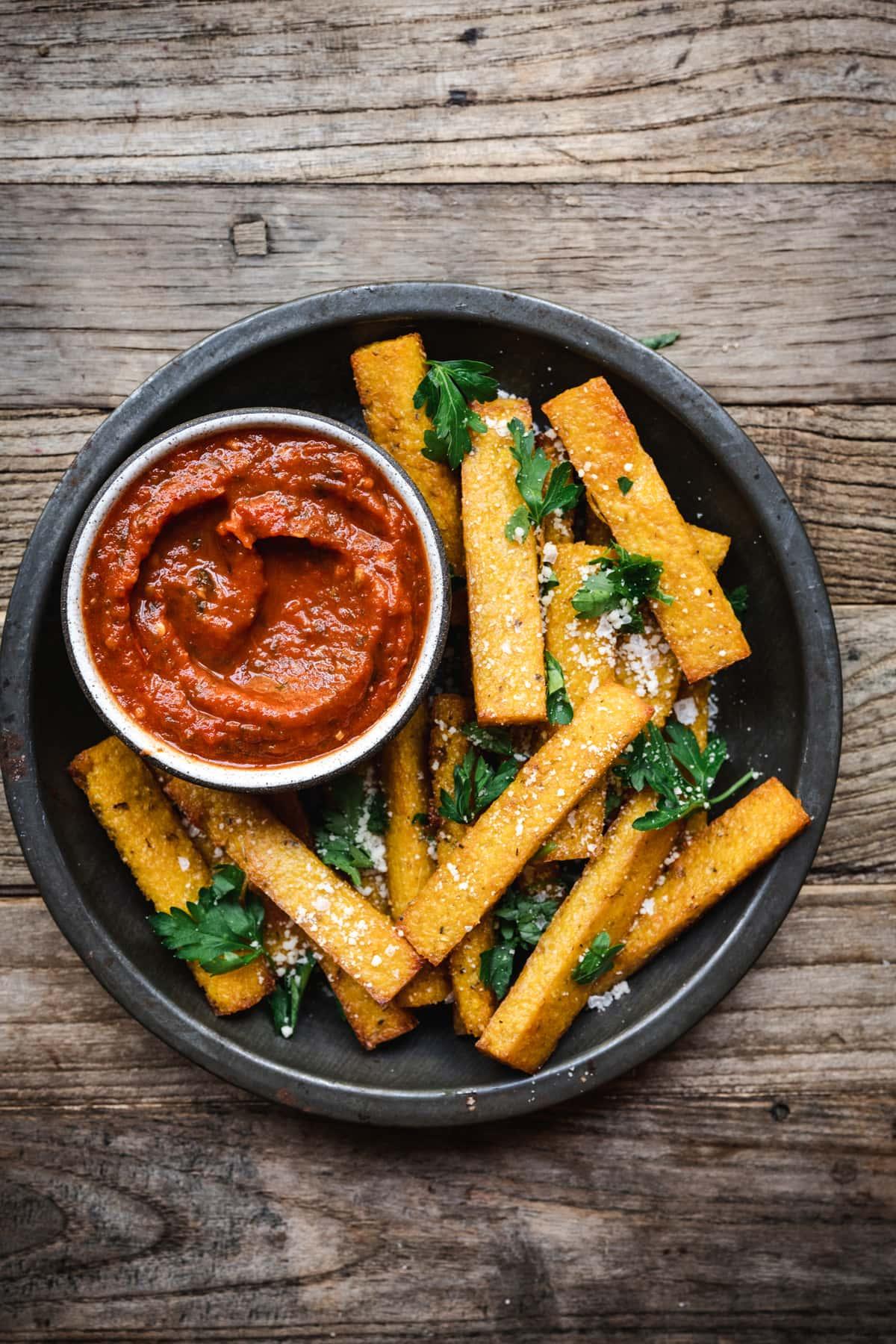 overhead of vegan polenta fries in a serving dish with marinara sauce
