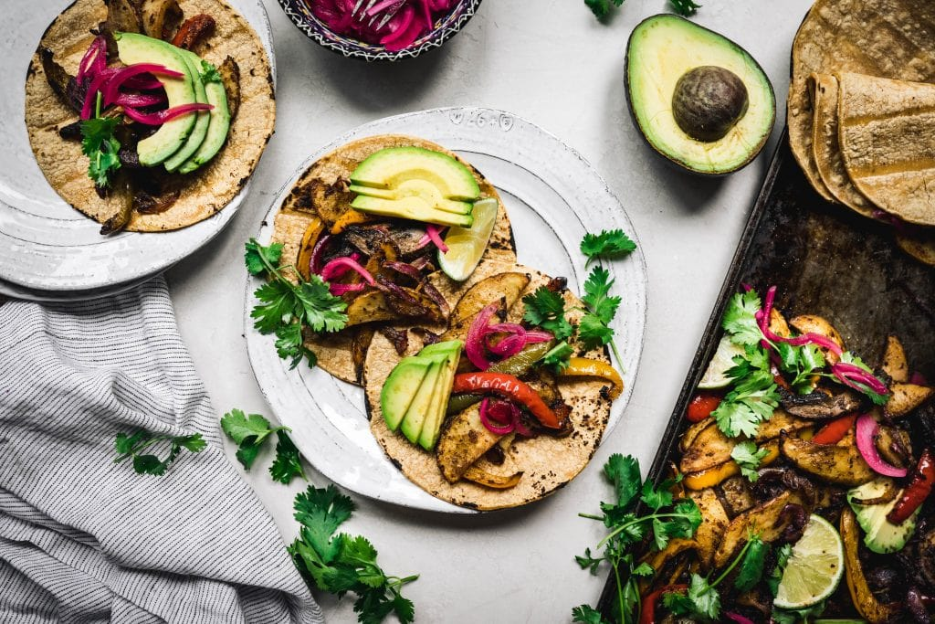 overhead of vegan portobello fajitas on plates with an avocado