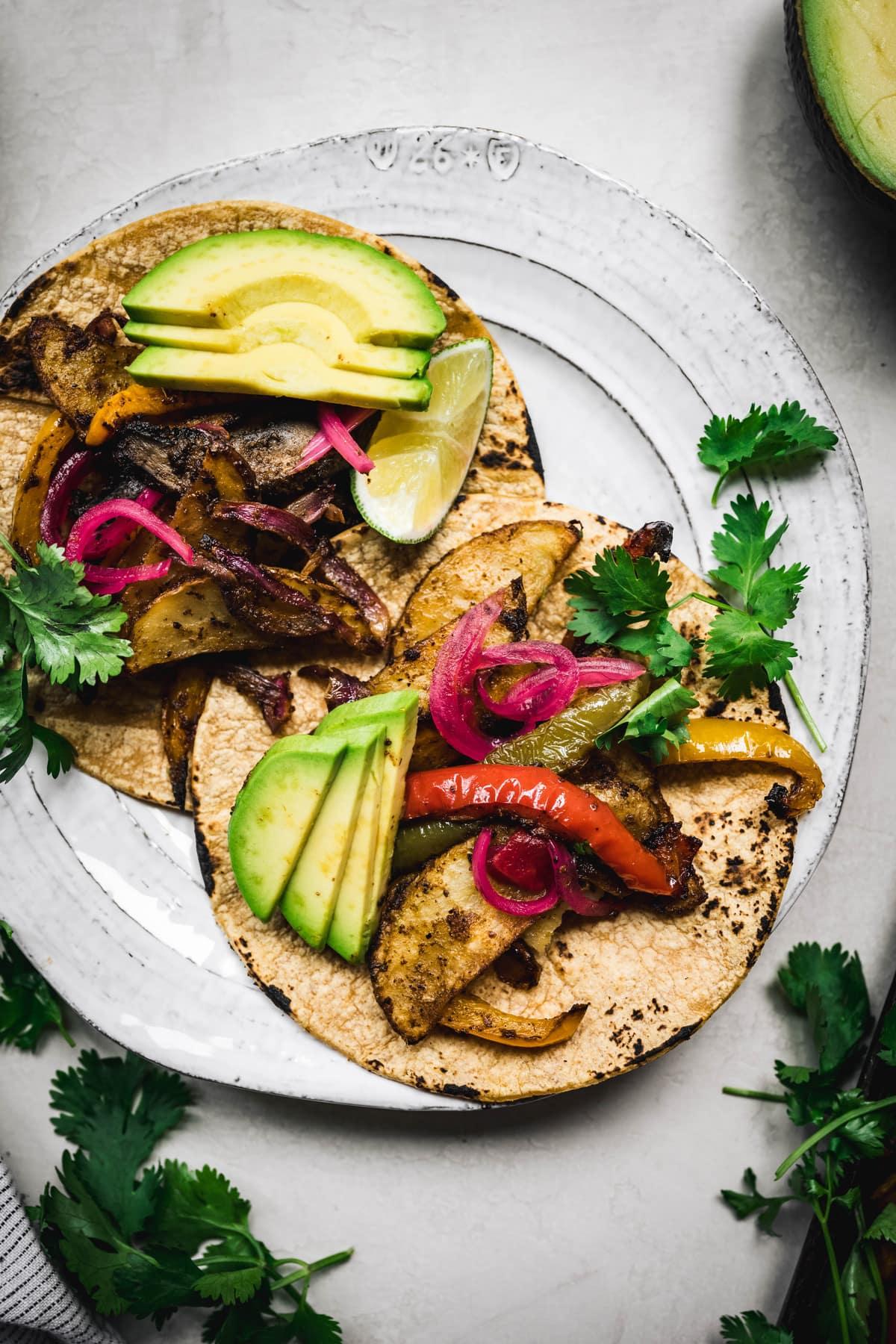 overhead of two vegan portobello fajitas on a white plate