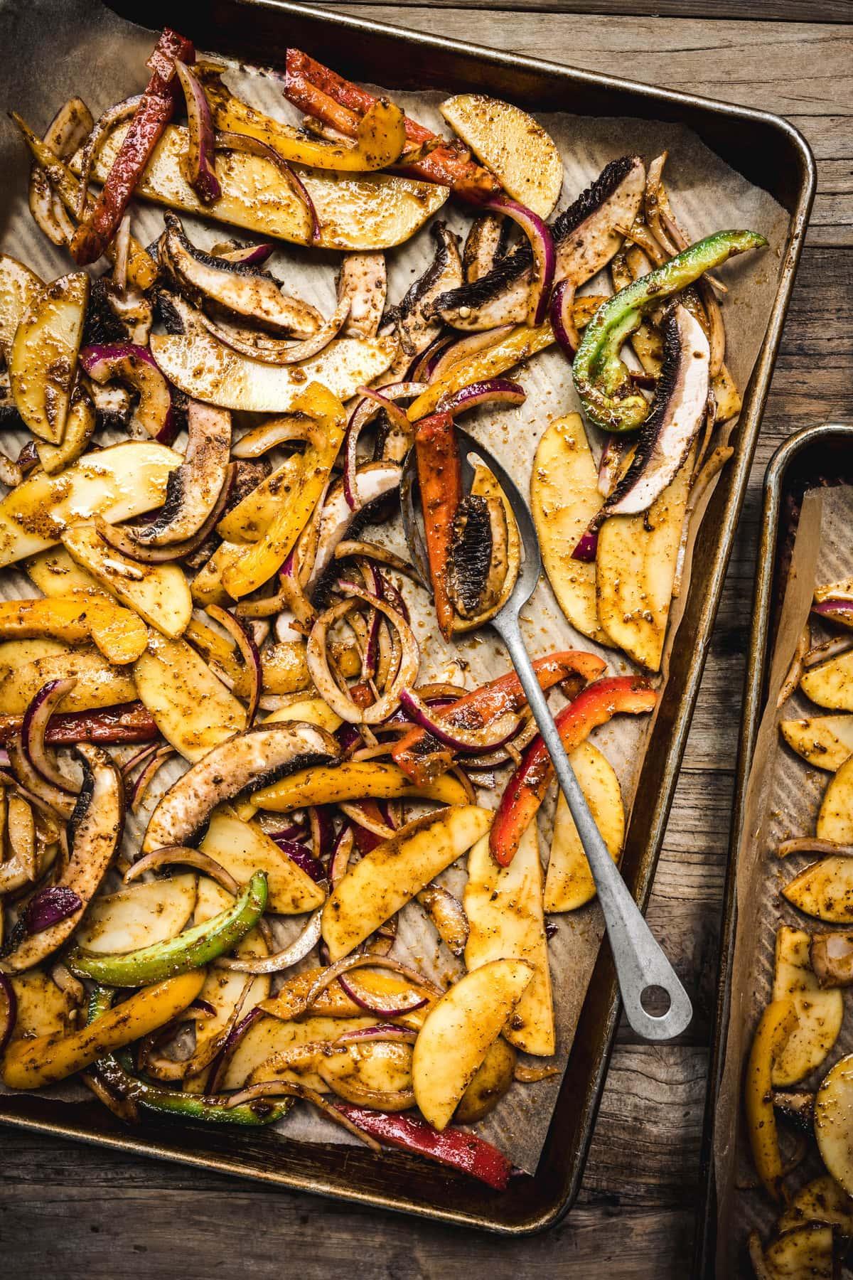 overhead of potatoes, peppers, onions and mushrooms with fajita seasoning on a sheet pan