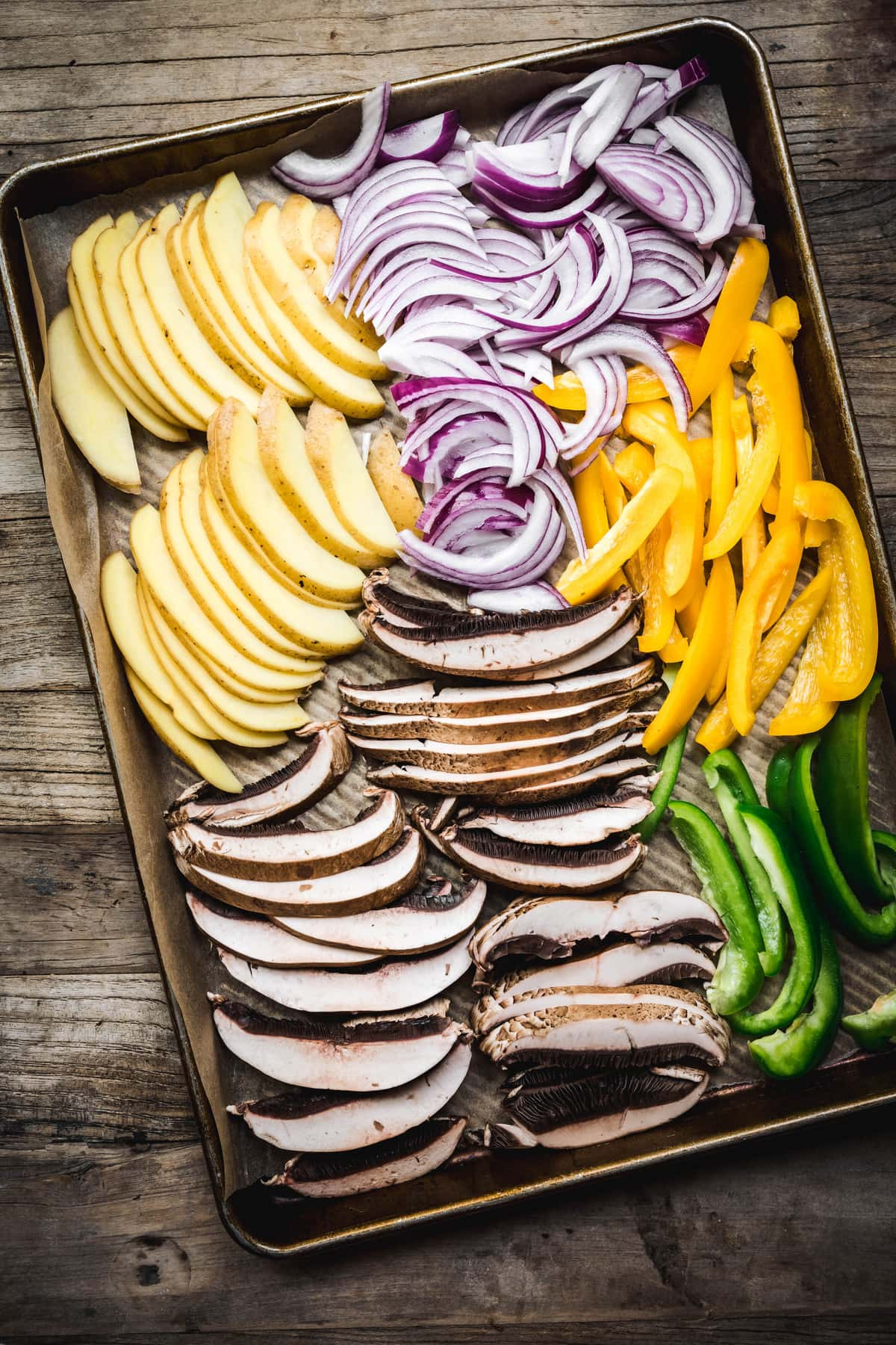 overhead of raw potatoes, portobellos, onions, and peppers on a sheet pan before cooking