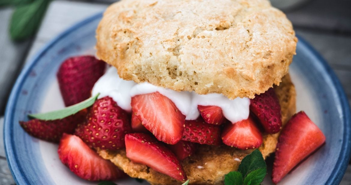 45 degree overhead of vegan strawberry shortcake on a blue and white plate outside on a picnic table