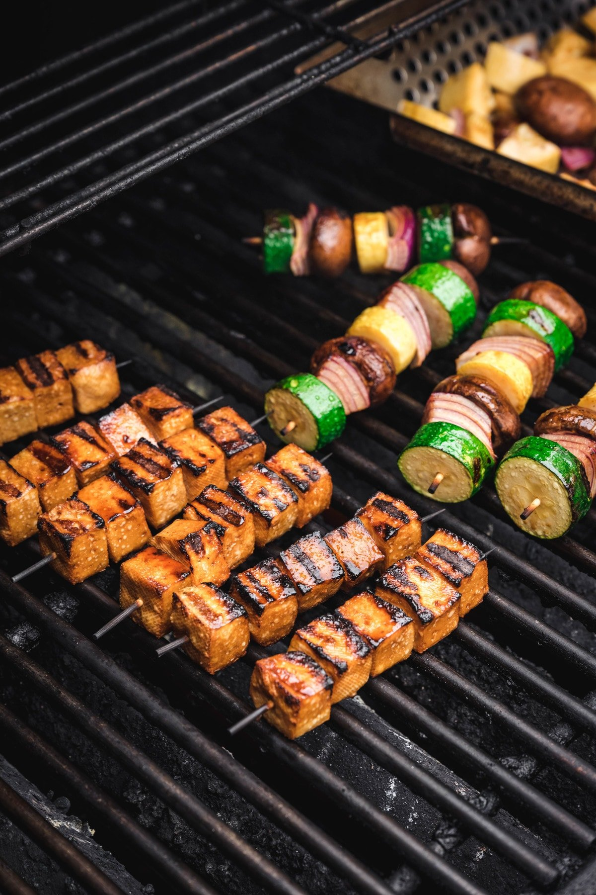 marinated tofu and vegetable kebabs cooking on a grill outside