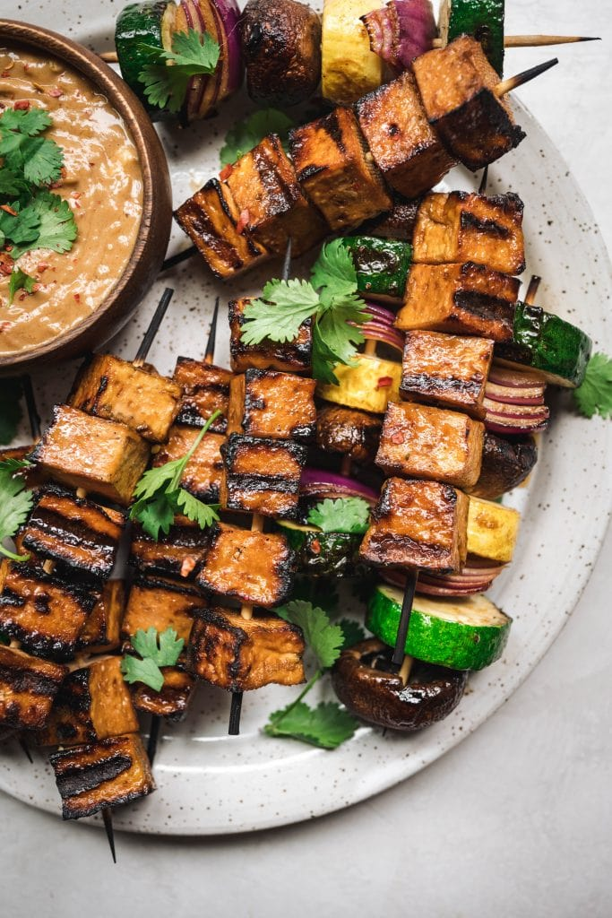 overhead of vegan tofu and vegetable kebabs on a plate with peanut sauce