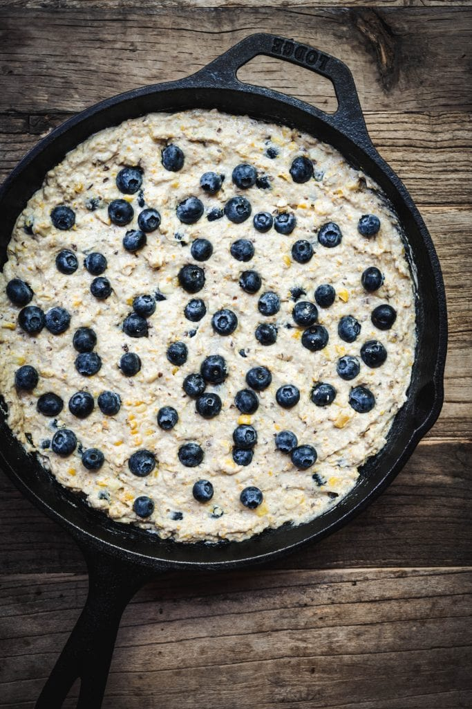 Overhead of blueberry cornbread in skillet before baking