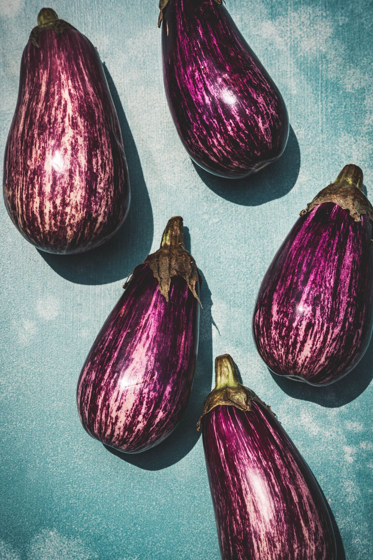 overhead of scicilian eggplants on a blue background