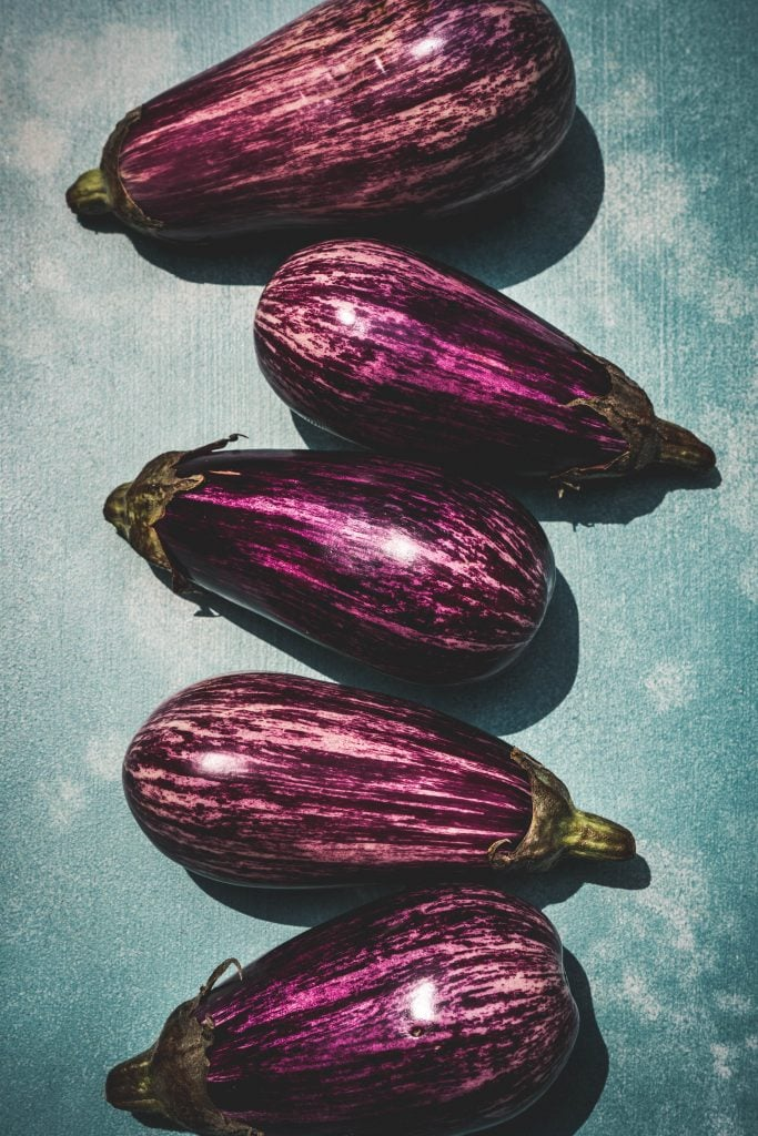 overhead of sciciian eggplants in a row on a blue background