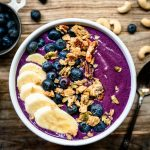 overhead of bluerry recovery smoothie bowl with banana and granola