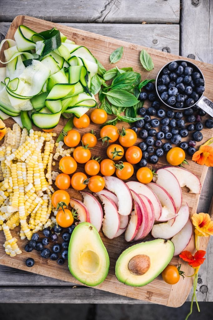 overhead of a wooden cutting board with fresh summer fruits and vegetables