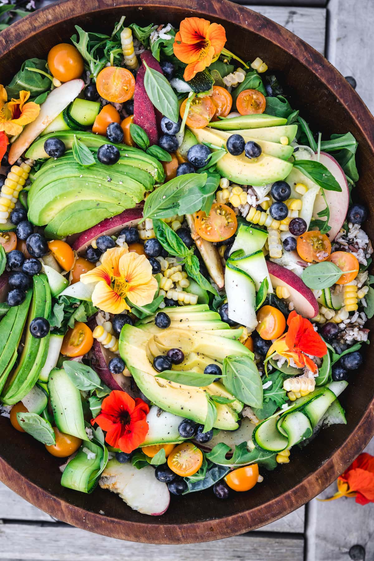 overhead close up of grain salad with fruits and vegetables in a wooden bowl outside