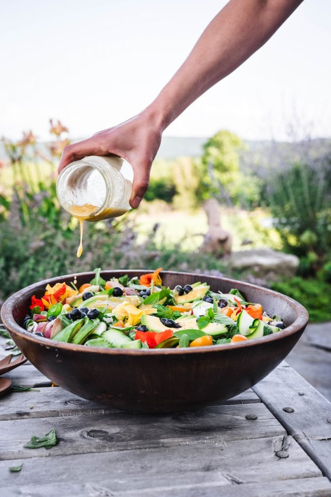 side view of someone pouring vinagrette over summer grain salad in a wooden serving bowl with green field in the background
