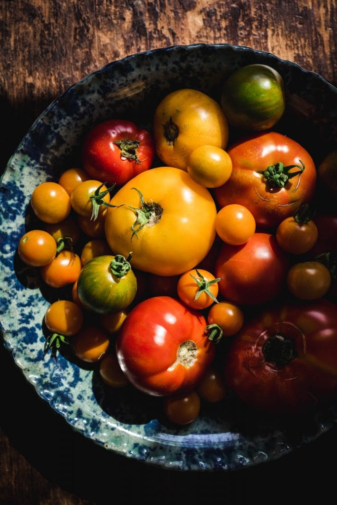 overhead of red yellow green and orange homegrown tomatoes in a speckled pie dish