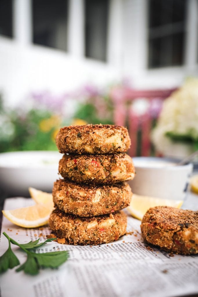 side view of a stack of four vegan crab cakes on newspaper