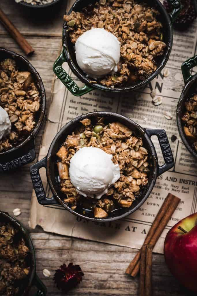 overhead of vegan apple crisp with vanilla ice cream on top