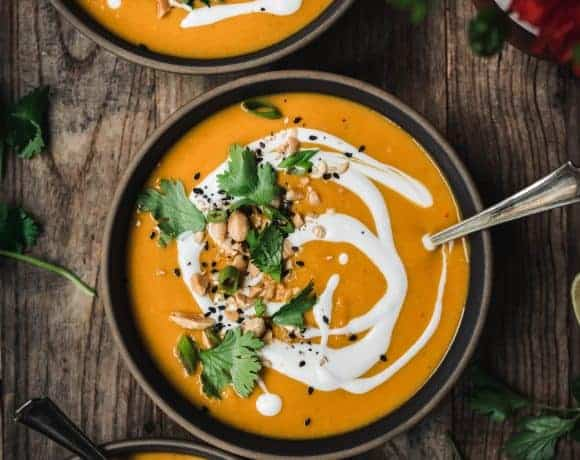 overhead view of three bowls of vegan butternut squash soup