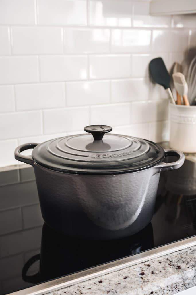side view of gray Le Creuset dutch oven on induction stovetop