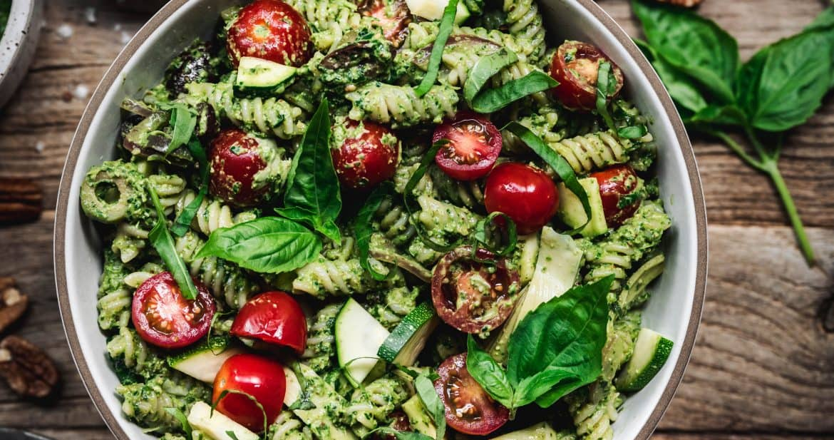 overhead view of pesto pasta salad with summer vegetables in white bowl