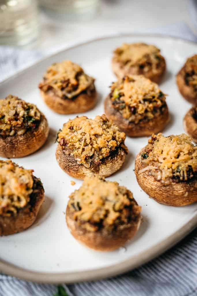 close up side view of vegan stuffed mushrooms on platter