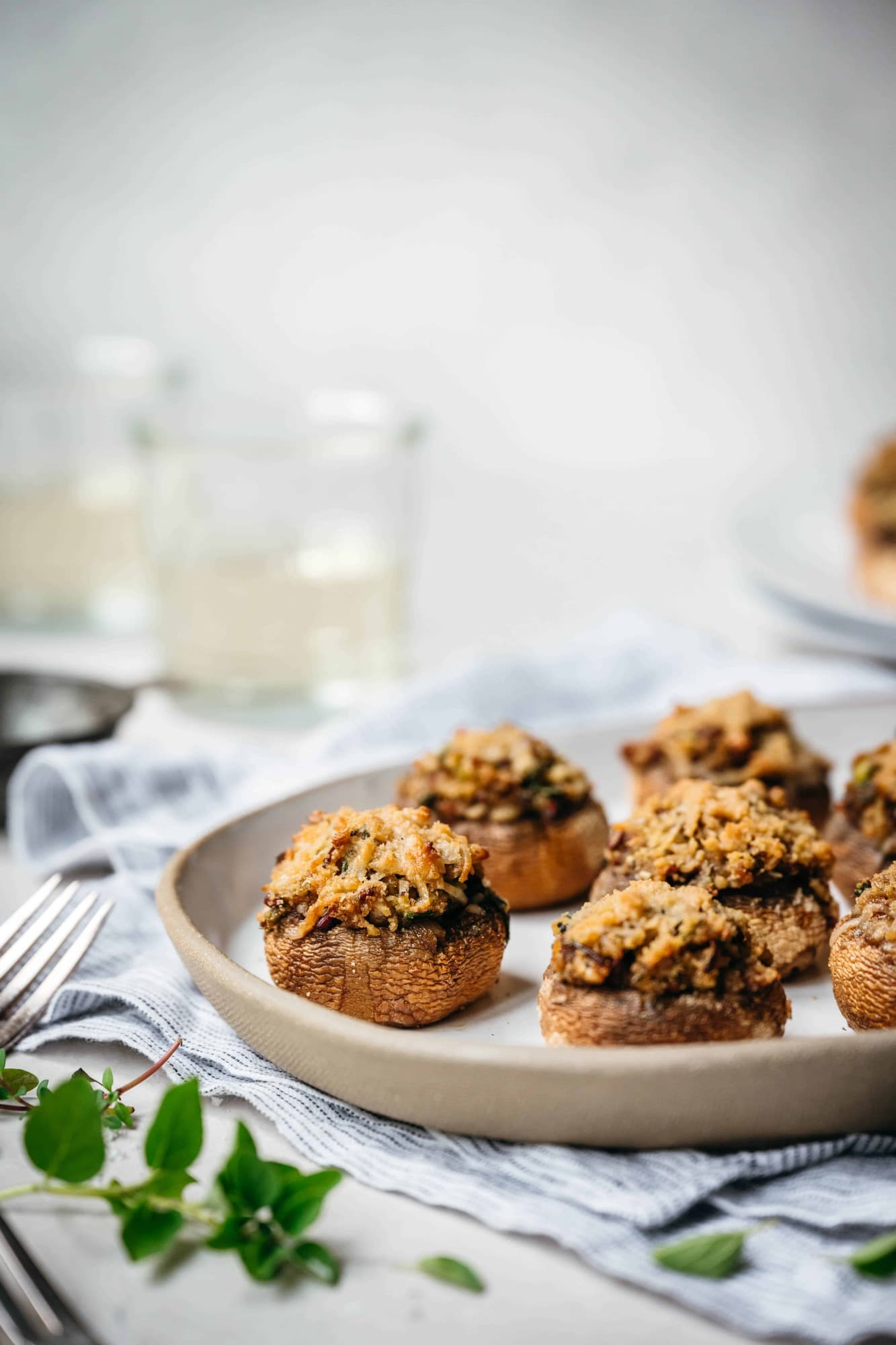 Side view of vegan stuffed mushrooms on a white platter