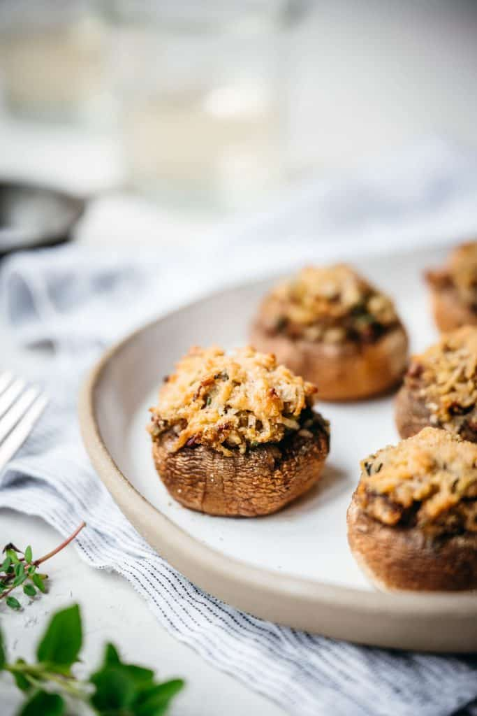 close up side view of vegan stuffed mushrooms on white platter
