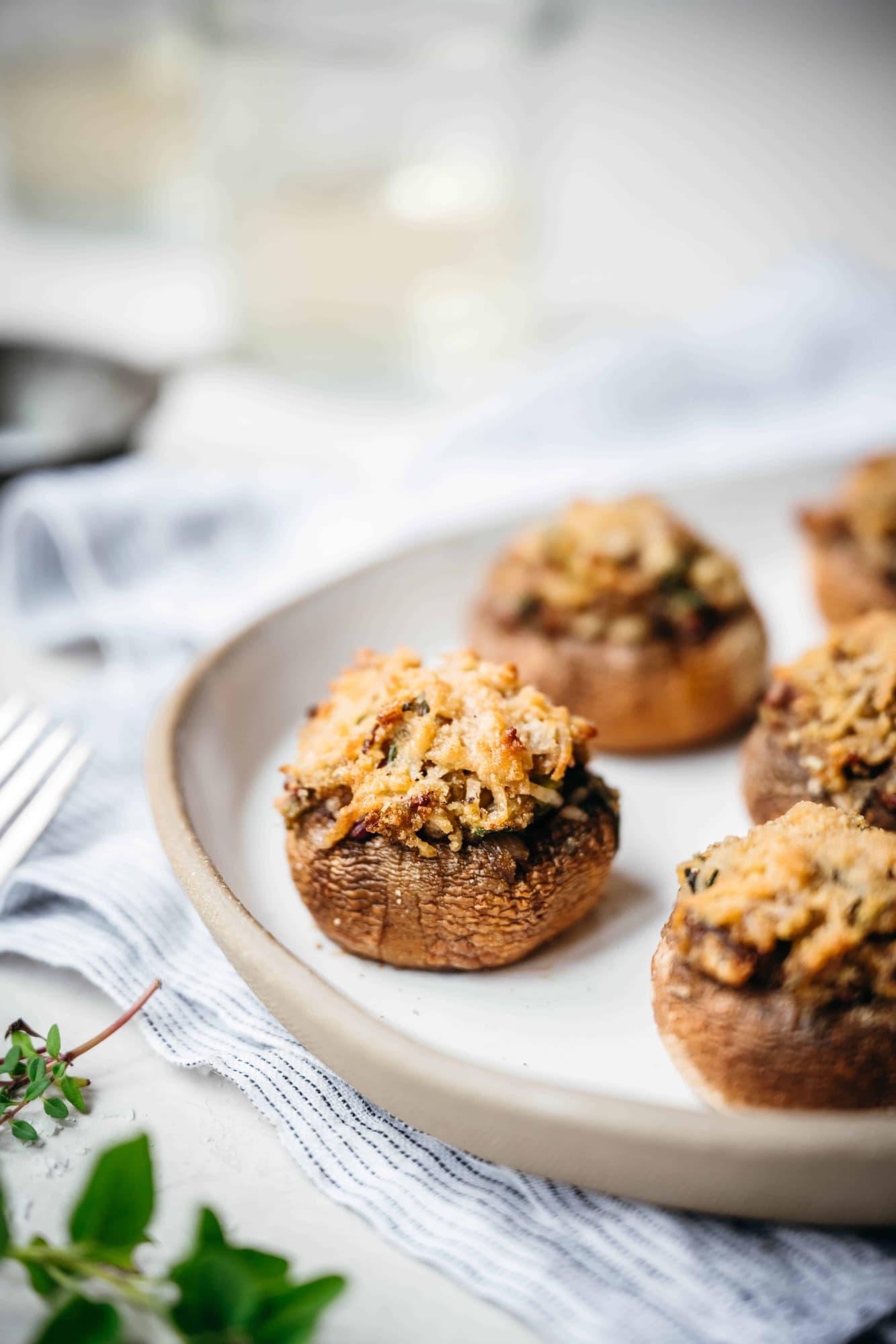 close up side view of vegan stuffed mushrooms on white platter