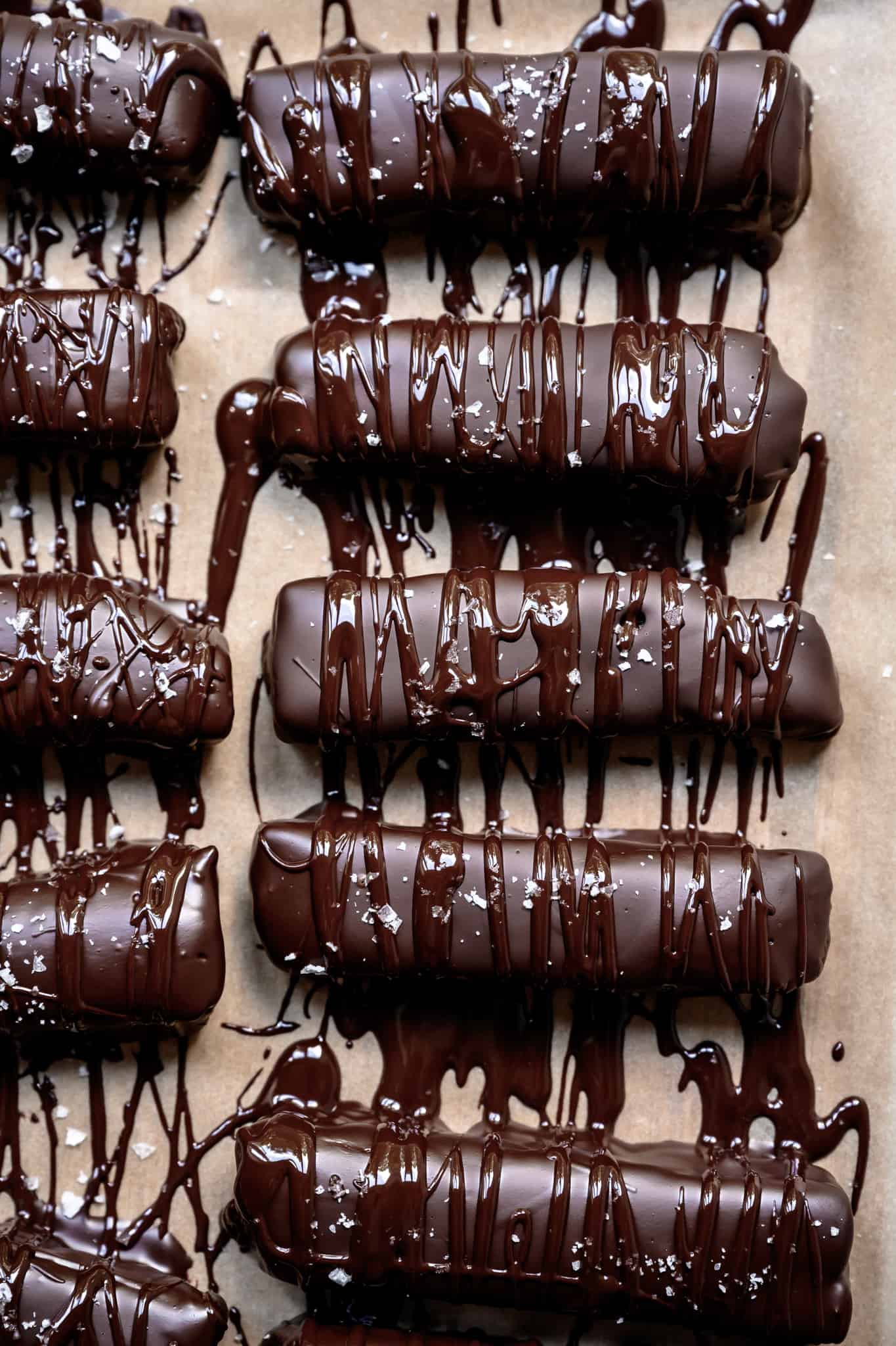overhead view of homemade twix bars with chocolate drizzle and salt on parchment paper