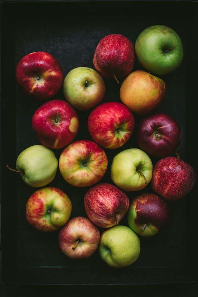 overhead view of beautiful multi-colored apples on a dark background