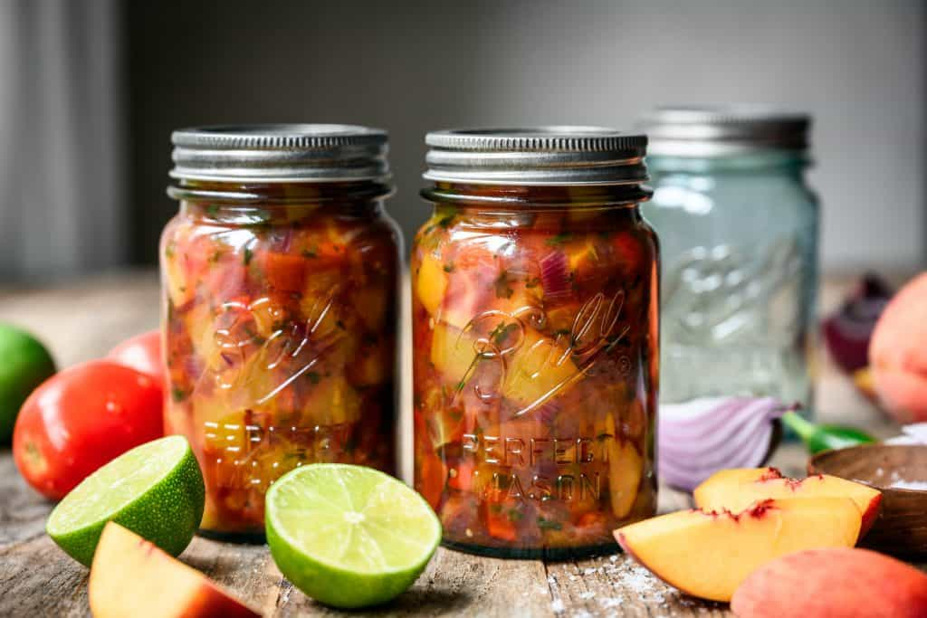 side view of peach tomato salsa in ball caning jars