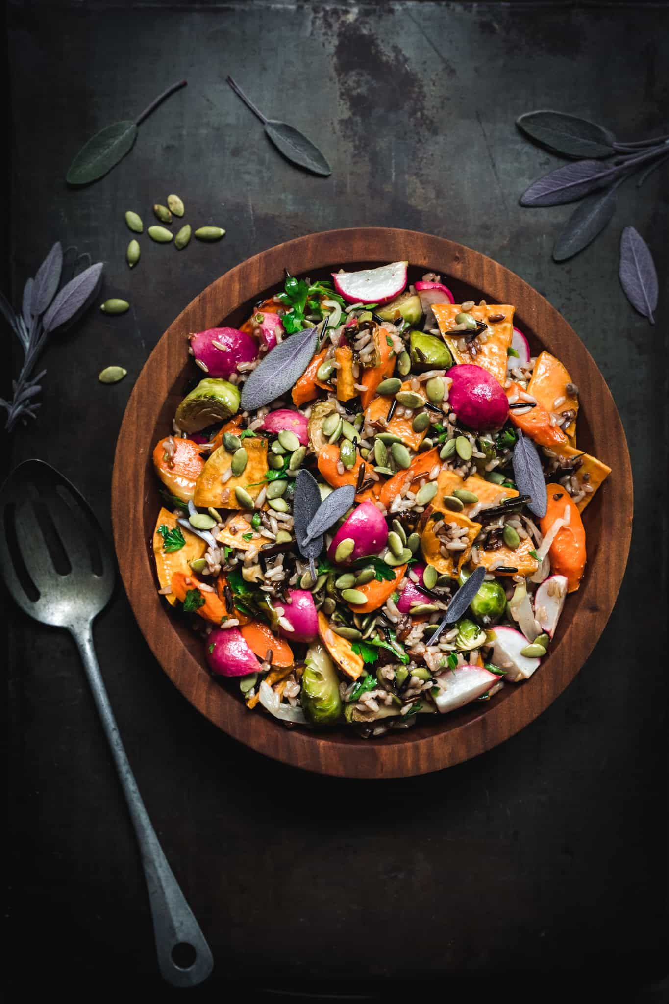 overhead of a bowl of harvest salad with wild rice and roasted vegetables in a wooden bowl