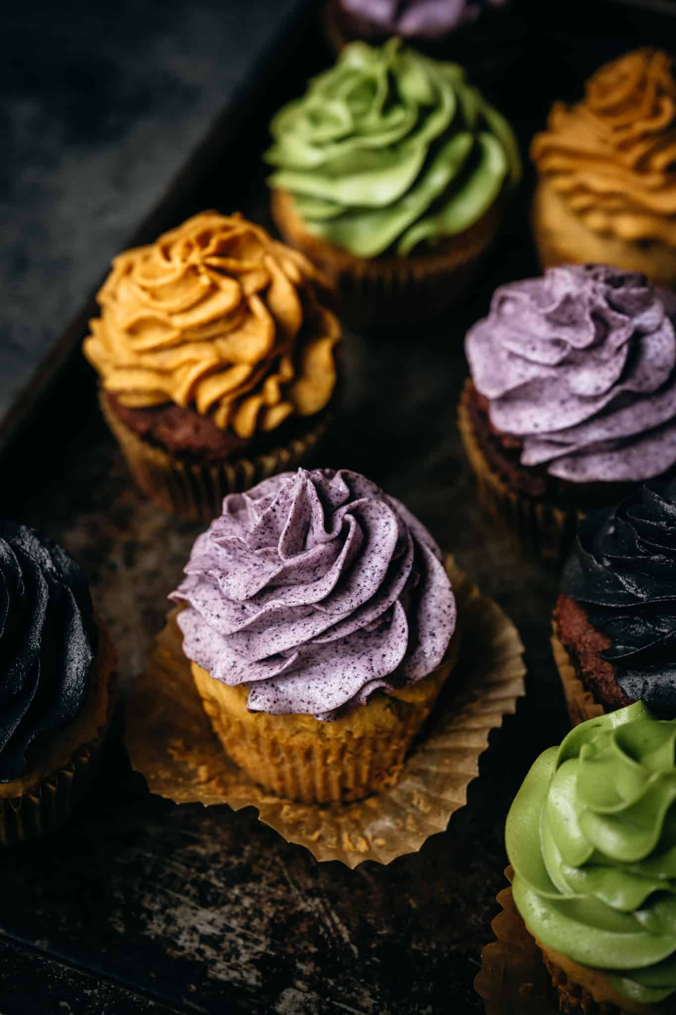 45 degree overhead of vegan cupcakes with naturally dyed buttercream frosting in purple, yellow and green