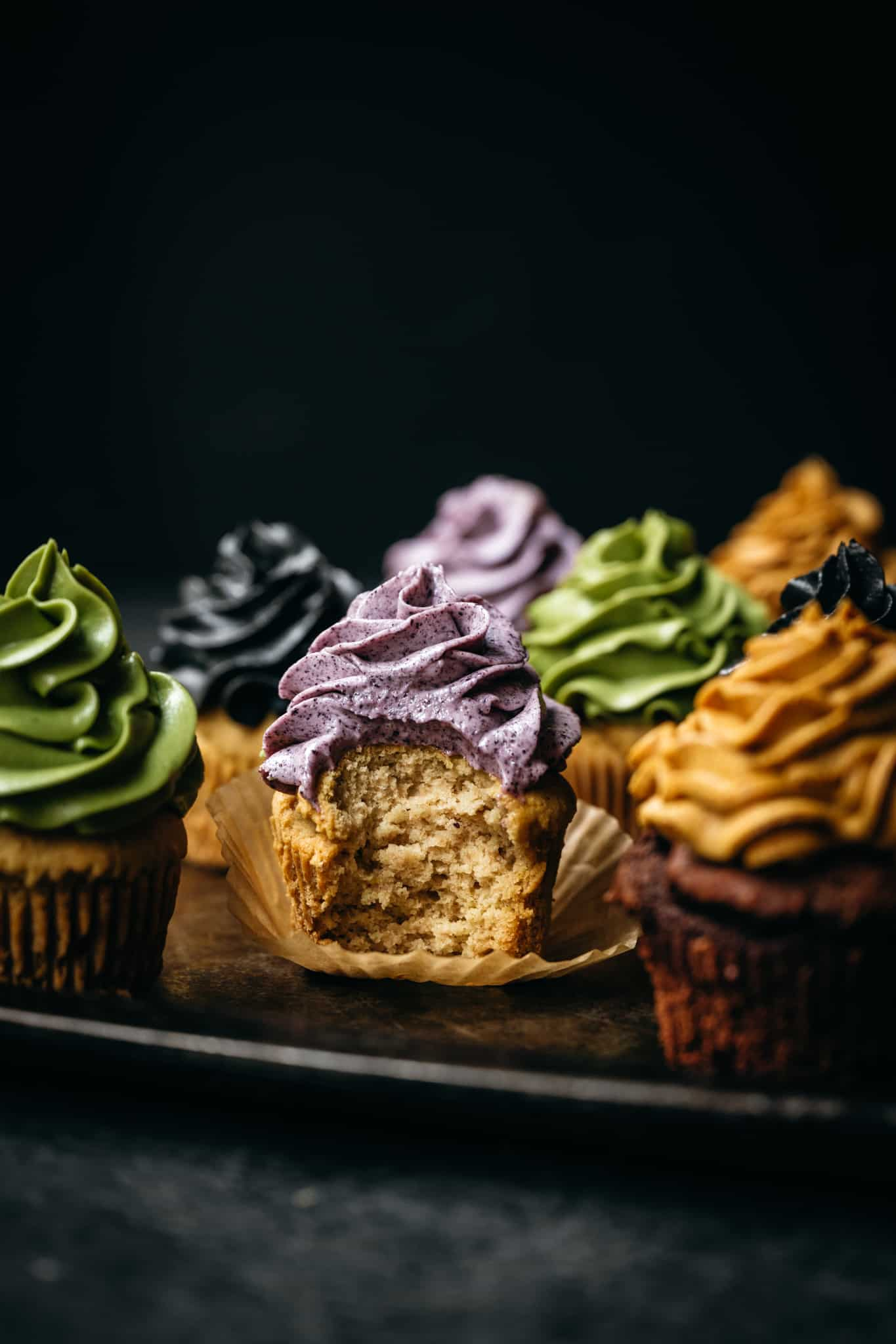 close up of vegan cupcakes topped with buttercream dyed with natural vegan food colorings with a bite taken out