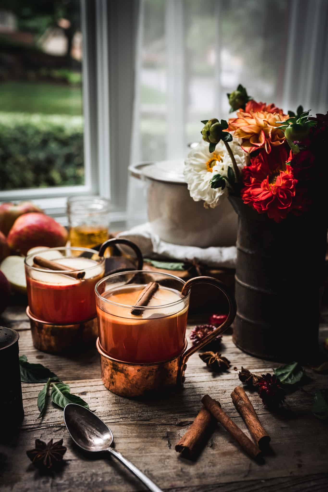 backlit side view of hot apple cider brandy cocktails with beautiful fall flowers
