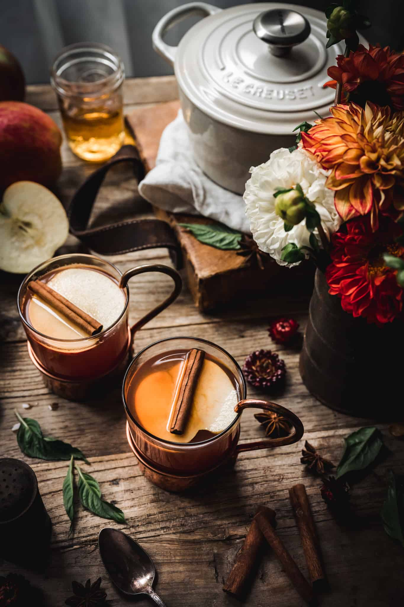 45 degree angle of hot apple cider brandy cocktail on wood backdrop