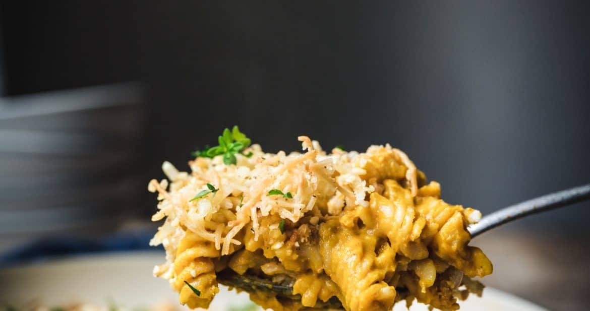 side view of person lifting vegan mac and cheese out of pan