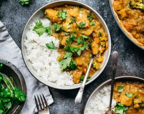 overhead of vegan pumpkin curry in smaller bowls with jasmine rice