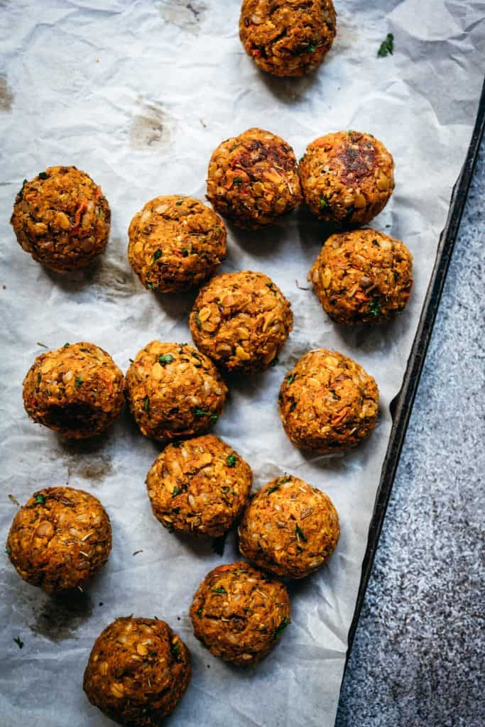 overhead view of homemade vegan lentil meatballs on sheet pan