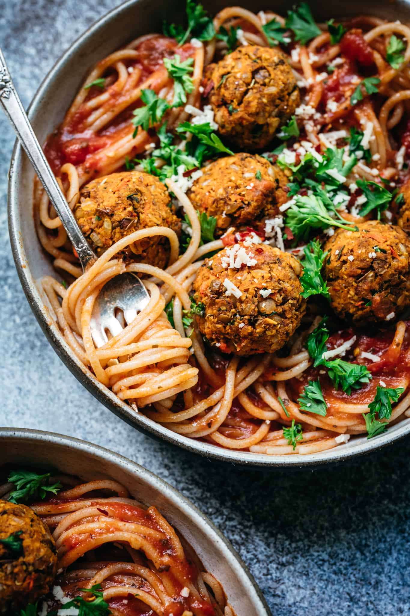 close up overhead of two bowls of spaghetti with vegan lentil meatballs and marinara sauce