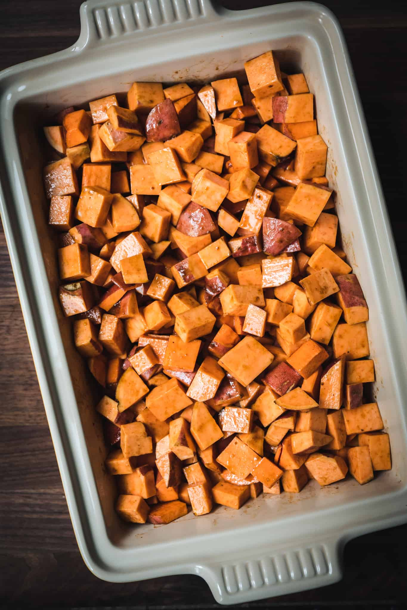 overhead view of diced sweet potatoes in casserole dish before baking