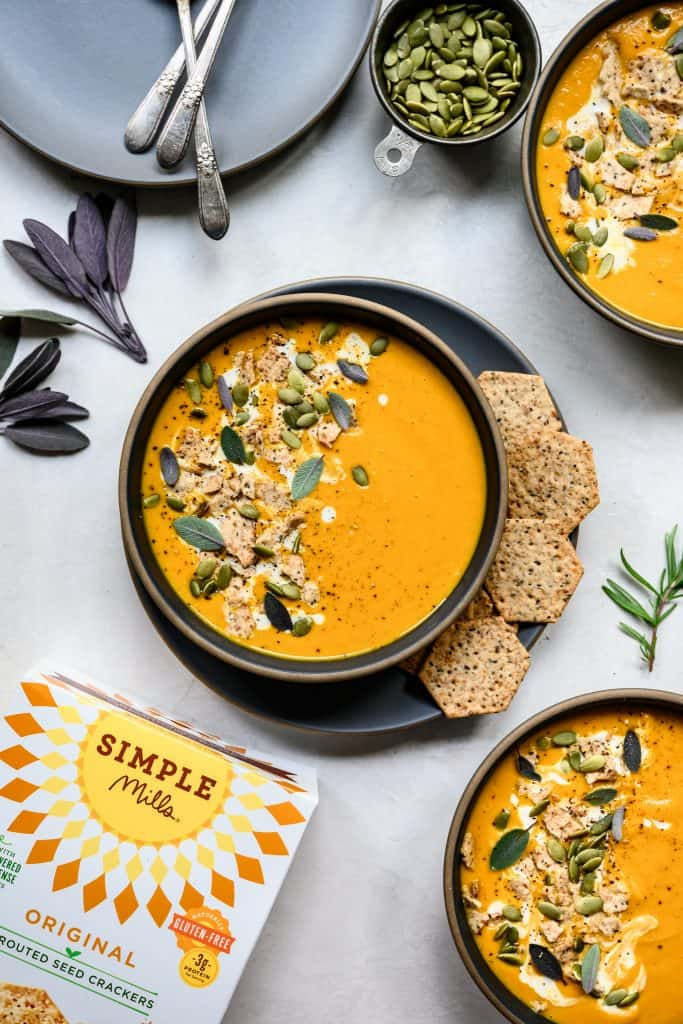 overhead view of vegan pureed carrot ginger soup with simple mills crackers on the side